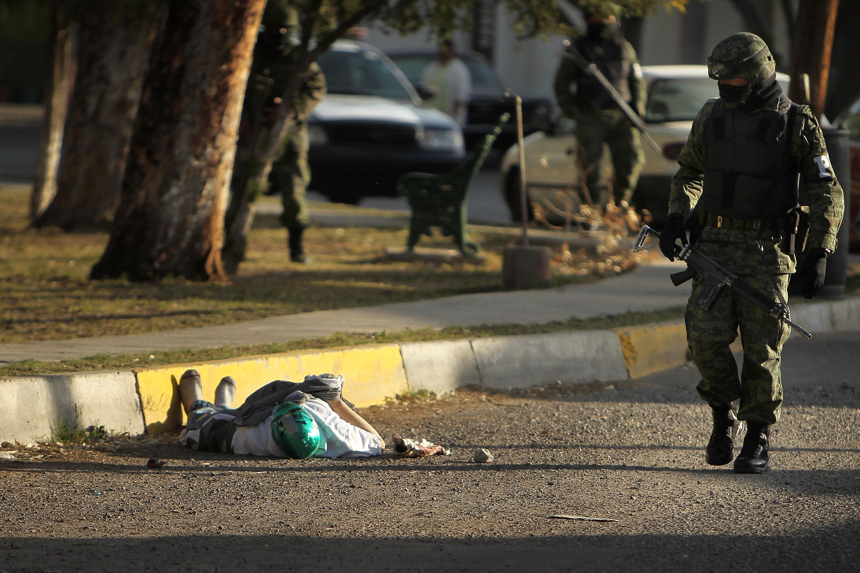 Сотрудник военной полиции возле тела одного из погибших в перестрелке боевых групп наркокартелей. Мексика, Хуарец, 2010 год (Фото - Getty Images)