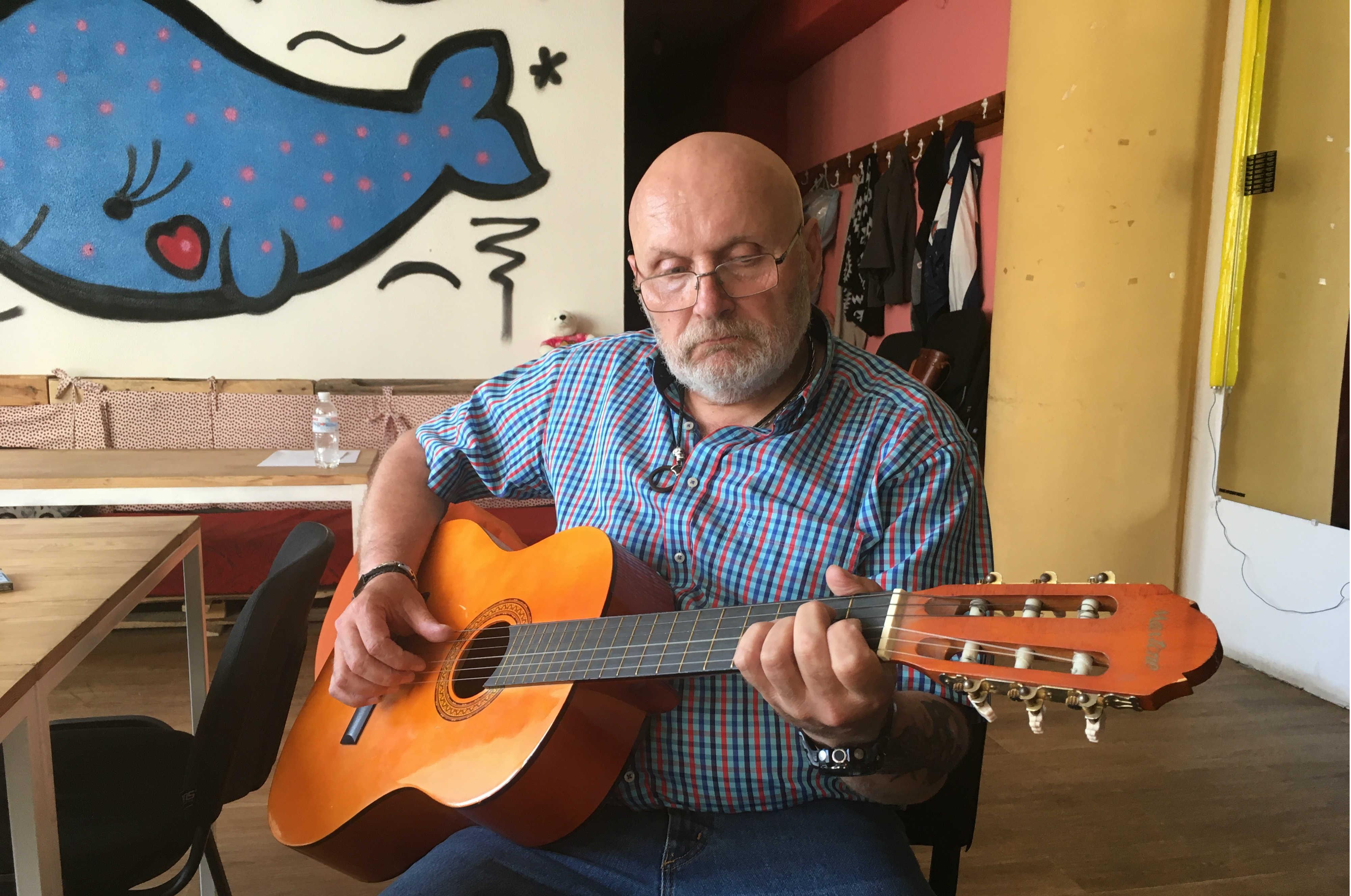 Игорь Стокоз играет на гитаре в обществнном центре Друзі в Константиновке (Фото Мелинды Хэринг)