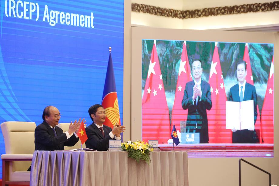 Премьер-министр Вьетнама Нгуен Суан Фук (слева) и министр промышленности и торговли Чан Туан Ань (справа) на прямой связи с Китаем, фото: LUONG THAI LINH / EPA
